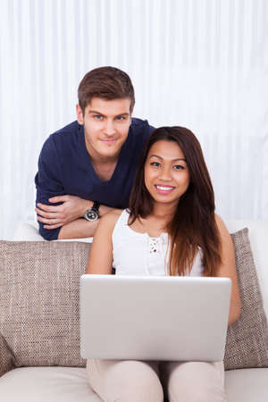 Portrait of smiling young couple with laptop in living room at home photo
