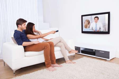 pareja viendo tv: Joven pareja viendo televisi�n mientras se est� sentado en el sof� en el sal�n de su casa