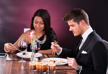 Welldressed young couple having meal at restaurant table photo