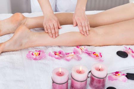 Beautician Waxing Womans Leg Applying Wax Strip photo