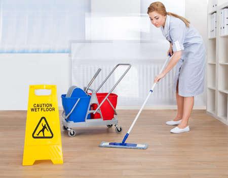 mujer limpiando: Retrato de joven mucama de limpieza de suelos con la fregona Foto de archivo