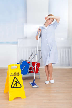 Tired Maid Cleaning Floor With Mop Over White Background photo