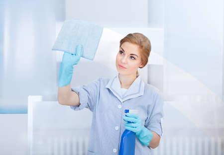 profesionálové: Portrét šťastná mladá služka čištění skel houbou