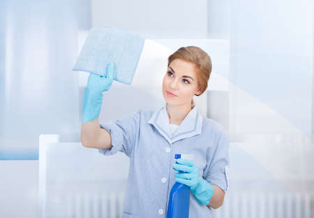 maid cleaning: Portrait Of Happy Young Maid Cleaning Glass With Sponge