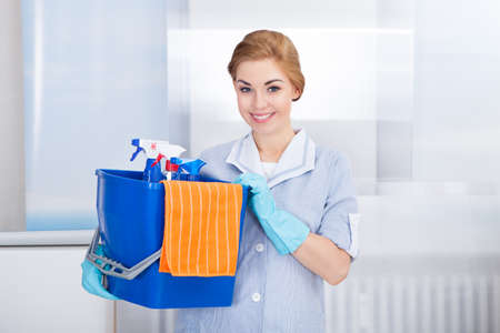 mujer limpiando: Feliz joven mucama Holding Compartimiento con las fuentes de limpieza Foto de archivo