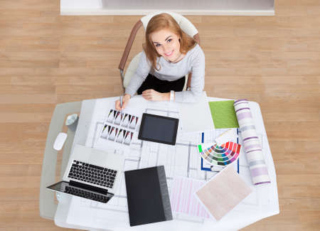 hands holding house: Portrait Of A Young Woman Working At Office Desk