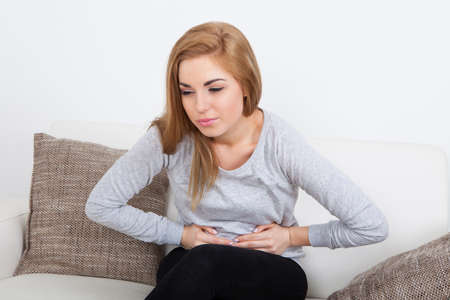 stomachache woman: Portrait Of Young Woman With Pain In Her Stomach Stock Photo