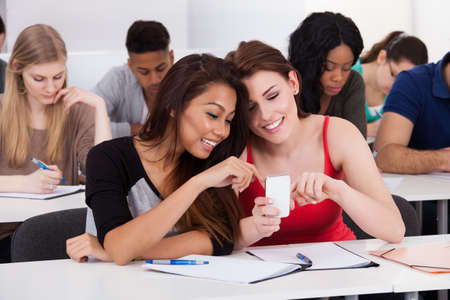 Happy female college students using mobile phone together at desk in classroom photo