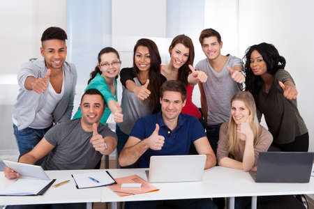 Group portrait of multiethnic college students gesturing thumbs up sign together in classroom photo