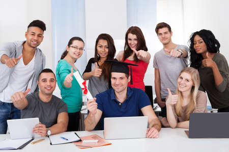 Portrait of college student holding degree with classmates gesturing thumbs up in classroom photo