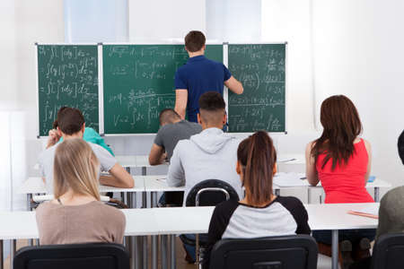 Rear view of teacher teaching mathematics to university students in classroom photo