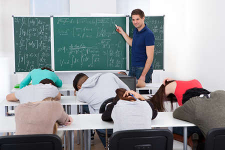 bored man: Young teacher teaching mathematics to bored college students in classroom