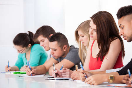 classmates: Row of multiethnic college students writing at desk in classroom