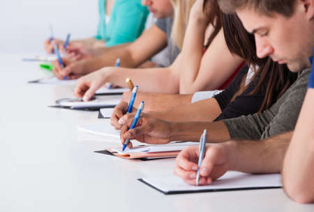 classmates: Cropped image of university students writing at desk in classroom Stock Photo