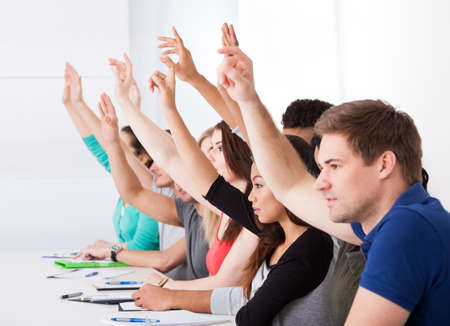 people voting: Row of multiethnic college students raising hands in classroom