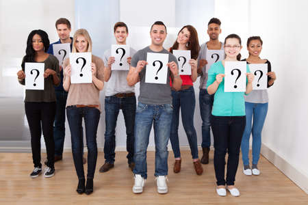Group portrait of confident college students holding question mark signs in classroom photo
