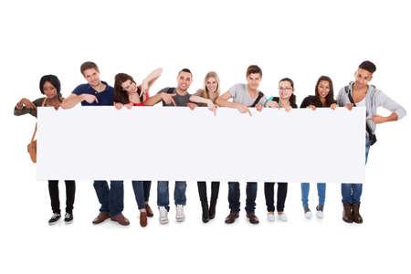 estudiantes universitarios: Retrato de cuerpo entero de los estudiantes universitarios multiétnicas confianza que muestra la cartelera en blanco contra el fondo blanco