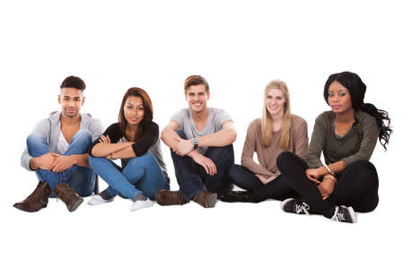 Full length portrait of multiethnic college students sitting in a row against white background photo