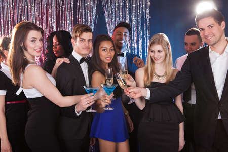 office party: Portrait of happy multiethnic friends toasting drinks at nightclub