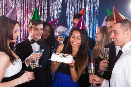 Beautiful young woman celebrating birthday with friends at nightclub photo