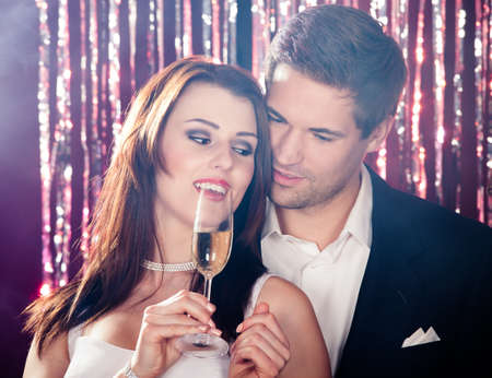 Romantic young couple enjoying champagne at nightclub photo