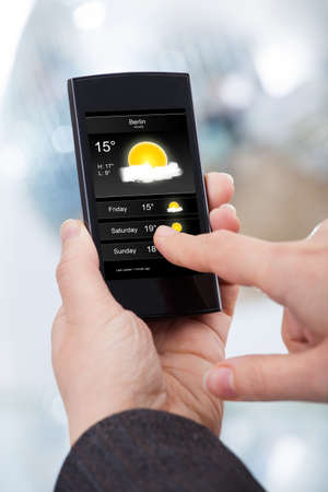 forecast: Cropped image of businesswoman checking weather forecast on smartphone in office Stock Photo