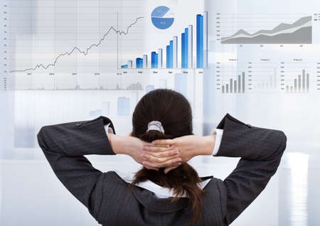 Rear view of businesswoman with hands behind head analyzing graphs in office photo