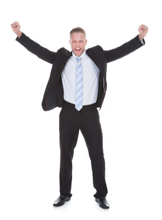 exultant: Exultant stylish young businessman in a suit standing cheering and raising his fists in the air as he celebrates a success  full length isolated on white Stock Photo