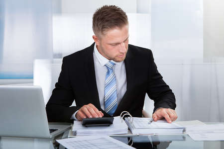 concentrates: Hardworking businessman analyzing a report sitting at his desk using a calculator and reading a report in a binder Stock Photo