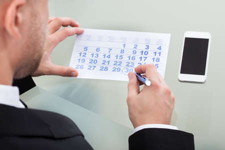 Businessman marking his dairy schedule checking for appointments and meetings as his mobile phone lies alongside the calendar  over the shoulder view Stock Photo