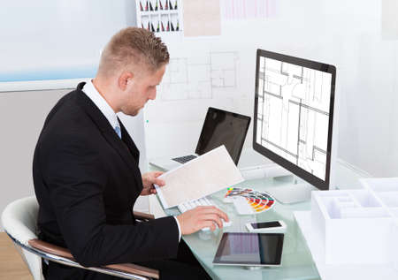 Businessman analyzing a spreadsheet online checking against a document in his hand to collate the information photo