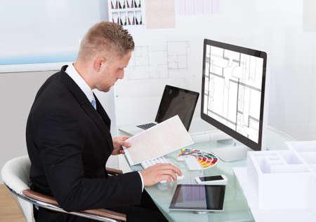 hoja de calculo: Negocios que analiza una cuenta de cheques en línea de hojas de cálculo en contra de un documento en la mano para cotejar la información