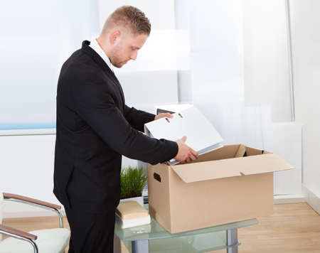 removals: Businessman moving offices packing up all his personal belongings and files into a brown cardboard box