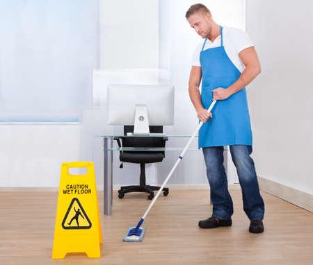 젖은: 청소부로 미끄러운 젖은 표면에 사람을주의하는 노란색 경고 통지 사무실 건물에서 바닥을 걸레