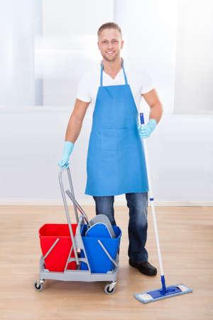 Hausmeister Reinigung von Holzböden mit einem Mopp und einem Wagen mit zwei Eimern für das Desinfektionsmittel und Wasser Pause in die Kamera zu lächeln, als er über seine Arbeit in einem Bürogebäude geht Standard-Bild