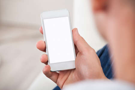 Over de schouder uitzicht op het lege scherm op een smartphone of mobiele telefoon gehouden in een mans hand Stockfoto