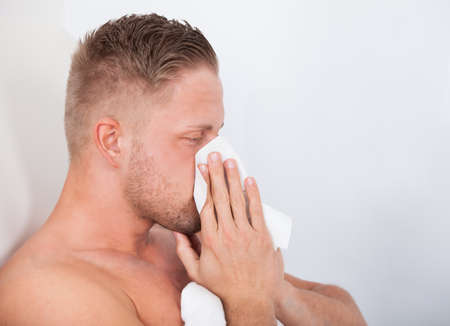 Man ill in bed with a seasonal cold or influenza blowing his nose on a tissue  side view close up Stock Photo - 27393724