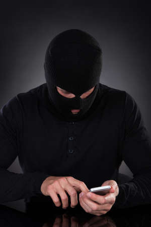surreptitious: Thief in a balaclava and black outfit standing in the darkness trying to access a stolen mobile phone or a terrorist activating a bomb remotely
