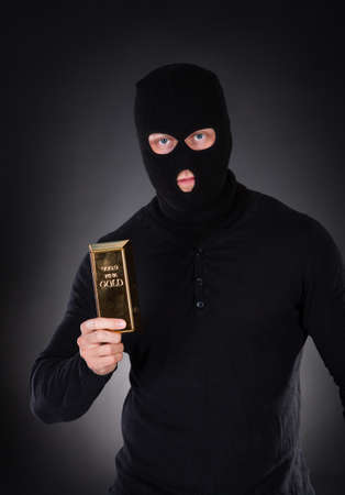 heist: Robber disguised in a black balaclava holding a gold bullion bar as he makes his getaway from a heist with the loot through the darkness