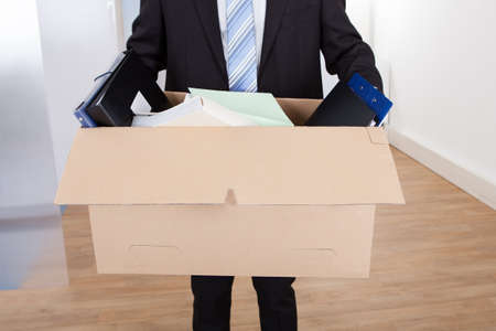 layoff: Midsection of businessman moving out with cardboard box from office