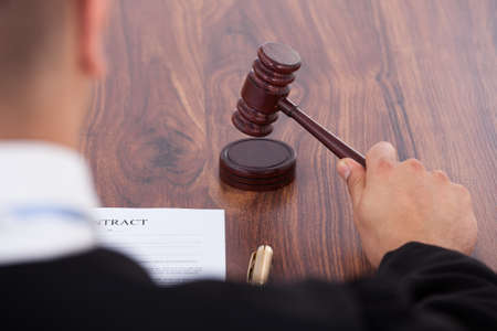 cropped image: Cropped image of judge knocking gavel in courtroom Stock Photo