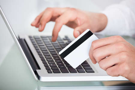 cropped image: Cropped image of man shopping with credit card and laptop