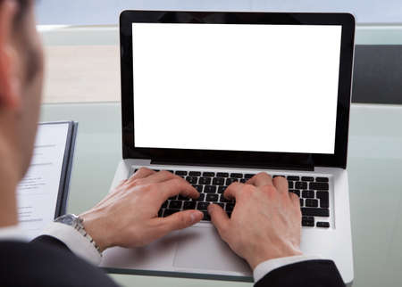 Cropped image of businessman using laptop at desk in office photo