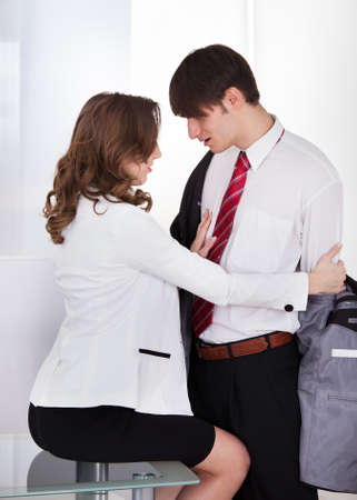 Young businesswoman undressing male colleague at desk in office photo