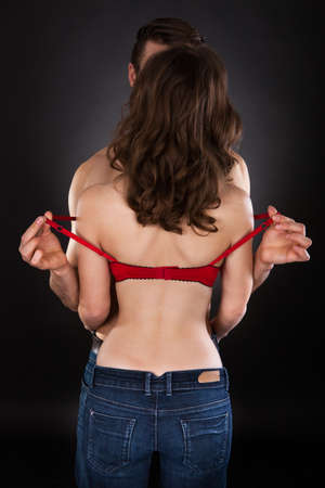 Boyfriend removing bra of girlfriend isolated over black background photo
