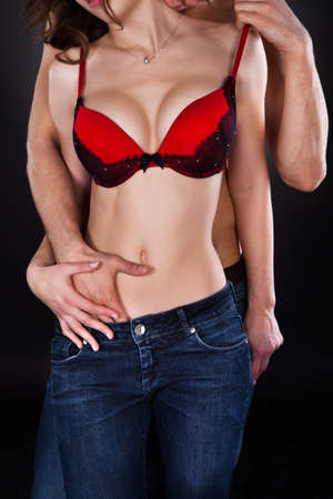 Passionate young man inserting hand in womans jeans while kissing her on neck isolated over black background photo