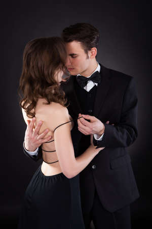 Passionate young man removing dress strap from womans shoulder isolated over black background photo