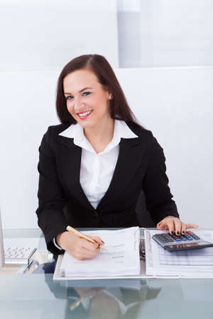 Portrait of happy businesswoman calculating tax at desk in office photo