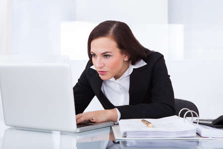 Concentrated young businesswoman using laptop at desk in office photo