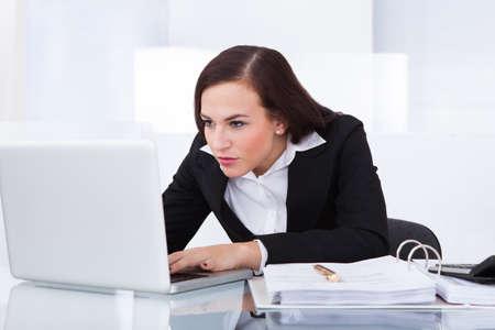 Geconcentreerde jonge zakenvrouw met behulp van laptop op het bureau in het kantoor Stockfoto